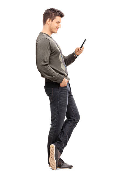 Young man texting on his cell phone Full length portrait of a young man texting on his cell phone isolated on white background leaning stock pictures, royalty-free photos & images