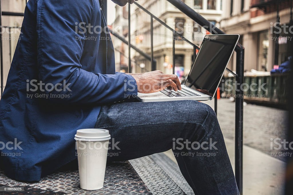 Young man texting on laptop stock photo