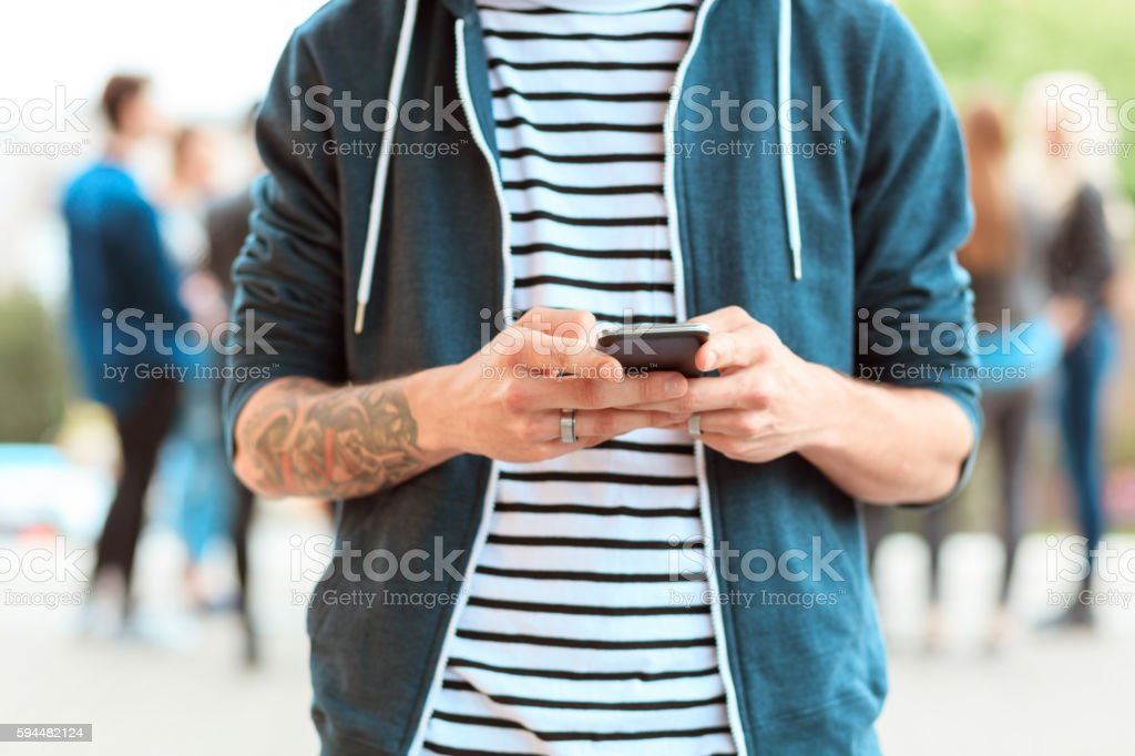 Young man texting on smart phone outdoor Young man texting on mobile outdoor. Group of people in the background. 20-29 Years Stock Photo