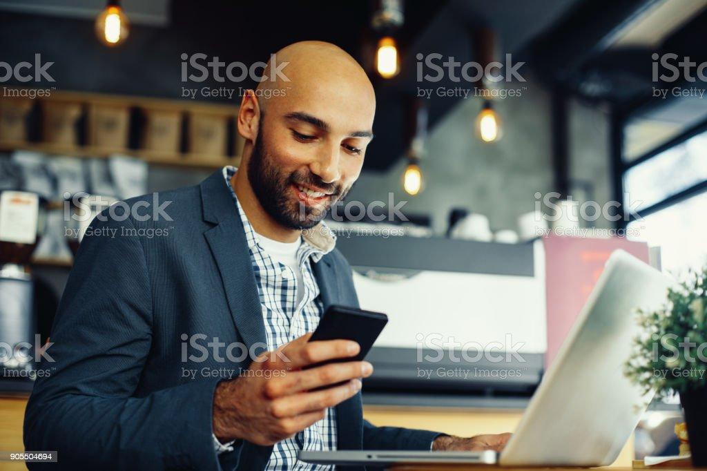 Junger Mann SMS auf dem Handy mit einem Laptop am Tisch im café – Foto