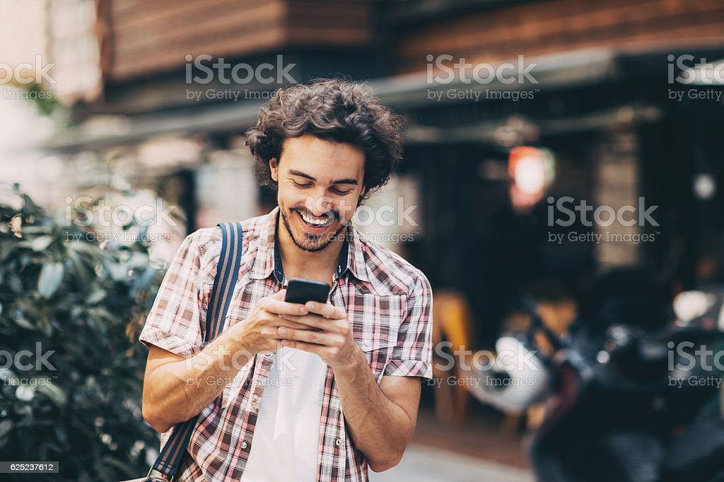 Young man texting on the street stock photo