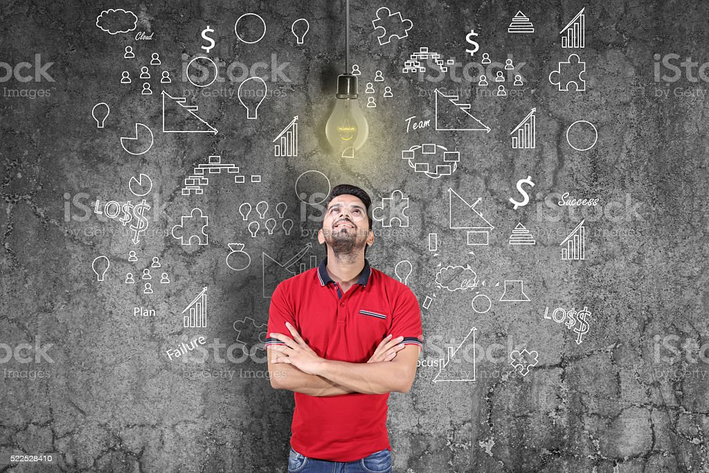 Young man thinking and looking at lightbulb stock photo