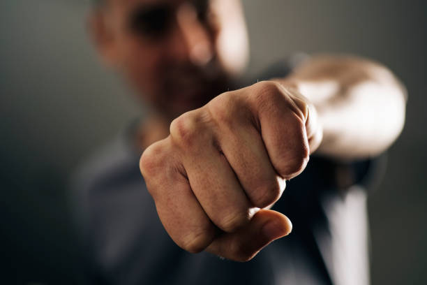 young man throwing a punch - aggression stock pictures, royalty-free photos & images