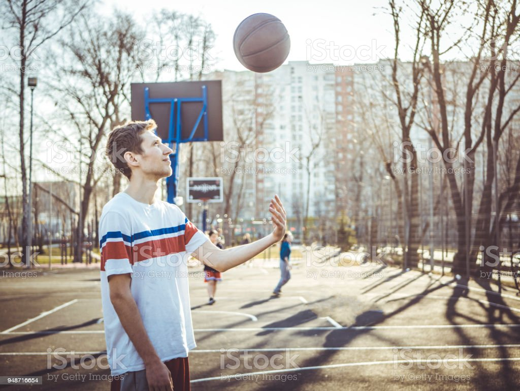 young man throwing the basketball up on the court