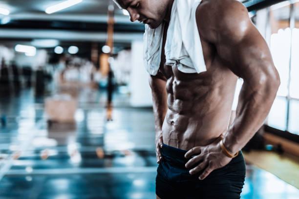 Jeune homme fatigué après l'entraînement, montrant ses muscles abdominaux. - Photo