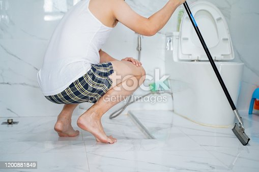 Back view of guy in home clothing sitting squat with mob in hard after hard clean up in toilet