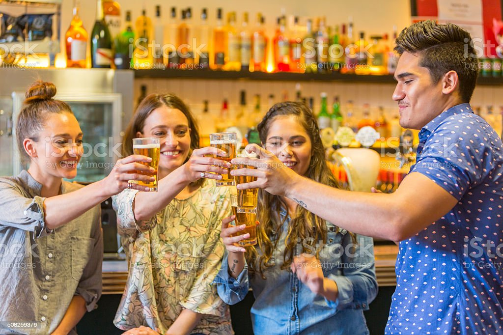 Young Man Toasting With Drinks and Girls in a Bar stock photo