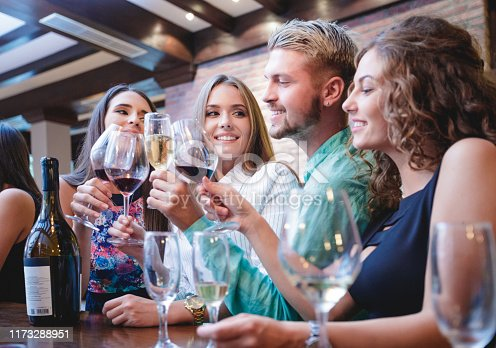 Young man proposing a toast to female friends with wine at winetasting party