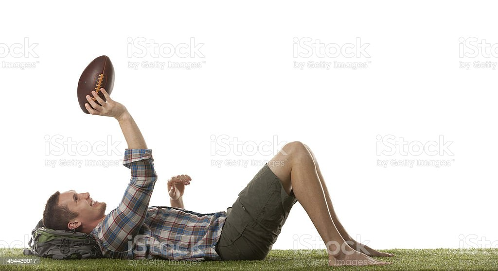 Young man tossing football while lying on grass royalty-free stock photo