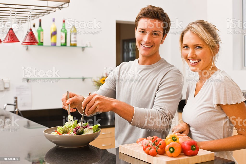 Young man tossing salad and woman cutting vegetable royalty-free stock photo