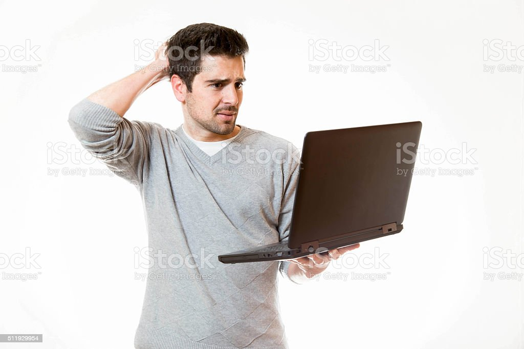 Young man touches his head wile working on his laptop stock photo
