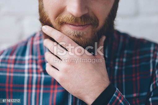 istock young man touches with hand his beard 611612212