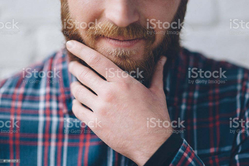young man touches with hand his beard - foto de stock