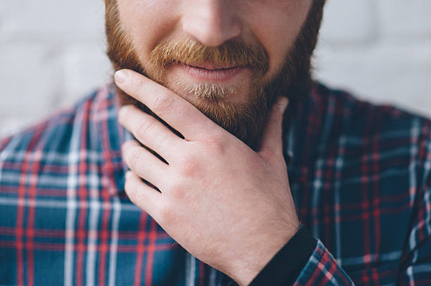young man touches with hand his beard stock photo