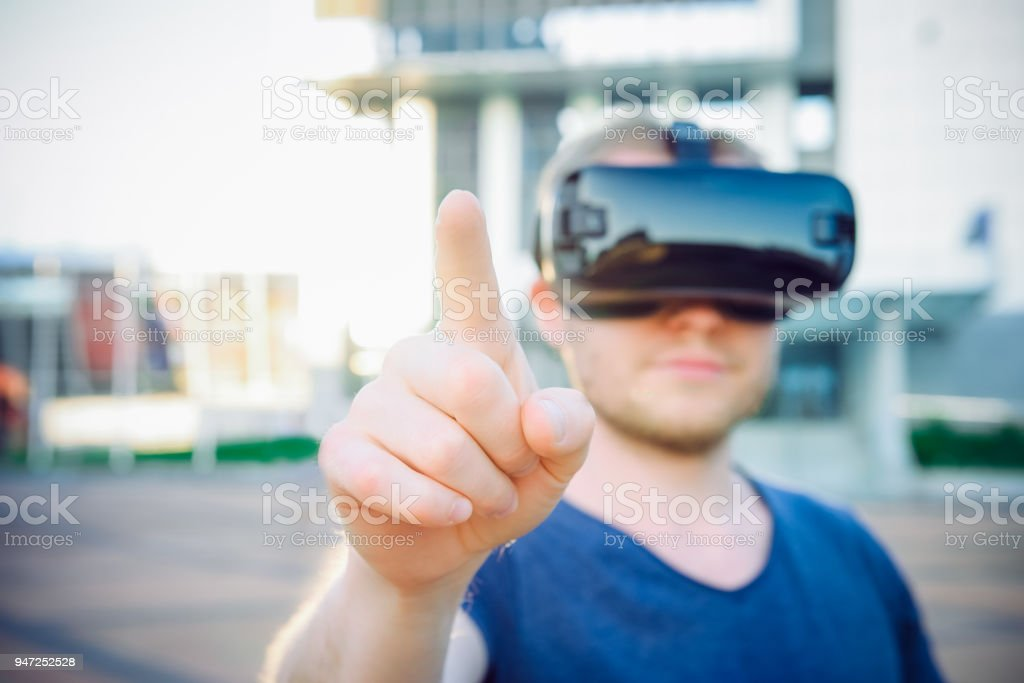 Young man touching space in front of him in virtual reality glasses headset standing against modern building background outdoors. Technology, innovation, cyberspace and gaming. Selective focus. stock photo