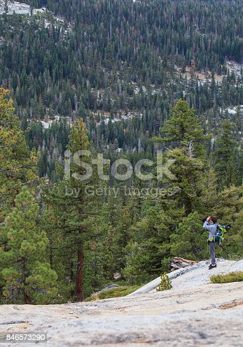 Young man, tourist - backpacker, with the huge backpack, walking across the Yosemite National Park along the Tioga Pass. Autumn, sunny warm October's day. California, USA, North America.