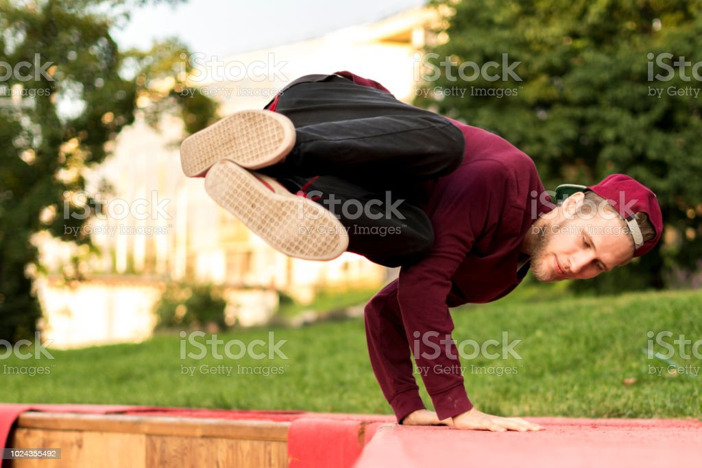 young man tracer in causual doing parkour in the city on a summer day