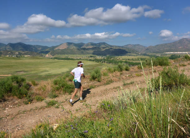 Running on top of Mount Carbon during a summer morning in the grasslands of Bear Creek Lake Park, a trail runner climbs the hill with the Front Range Rocky Mountains of Morrison in the backbround.