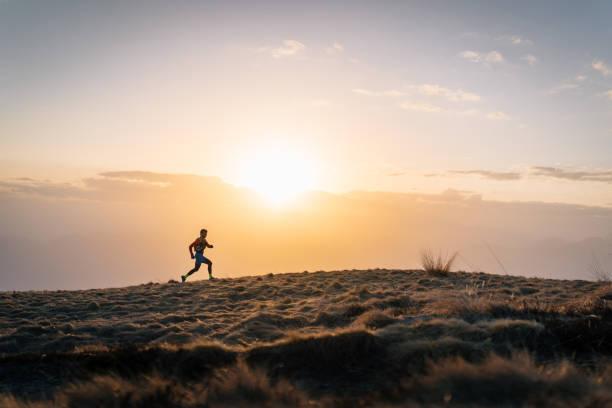 Young man trail runs up mountain at sunrise stock photo