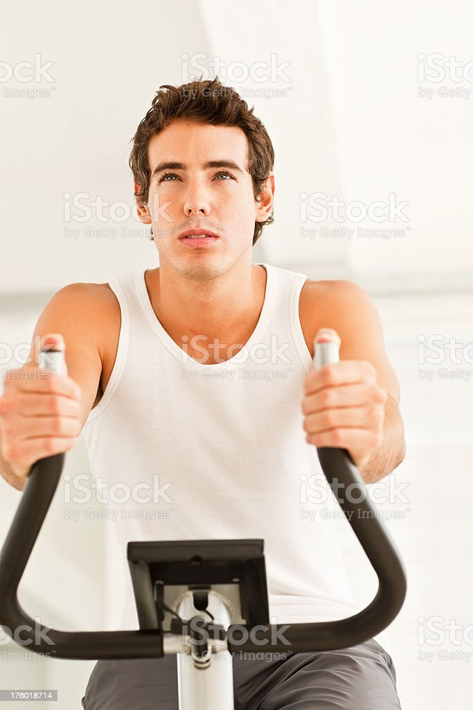 Young man training on an exercise bike royalty-free stock photo
