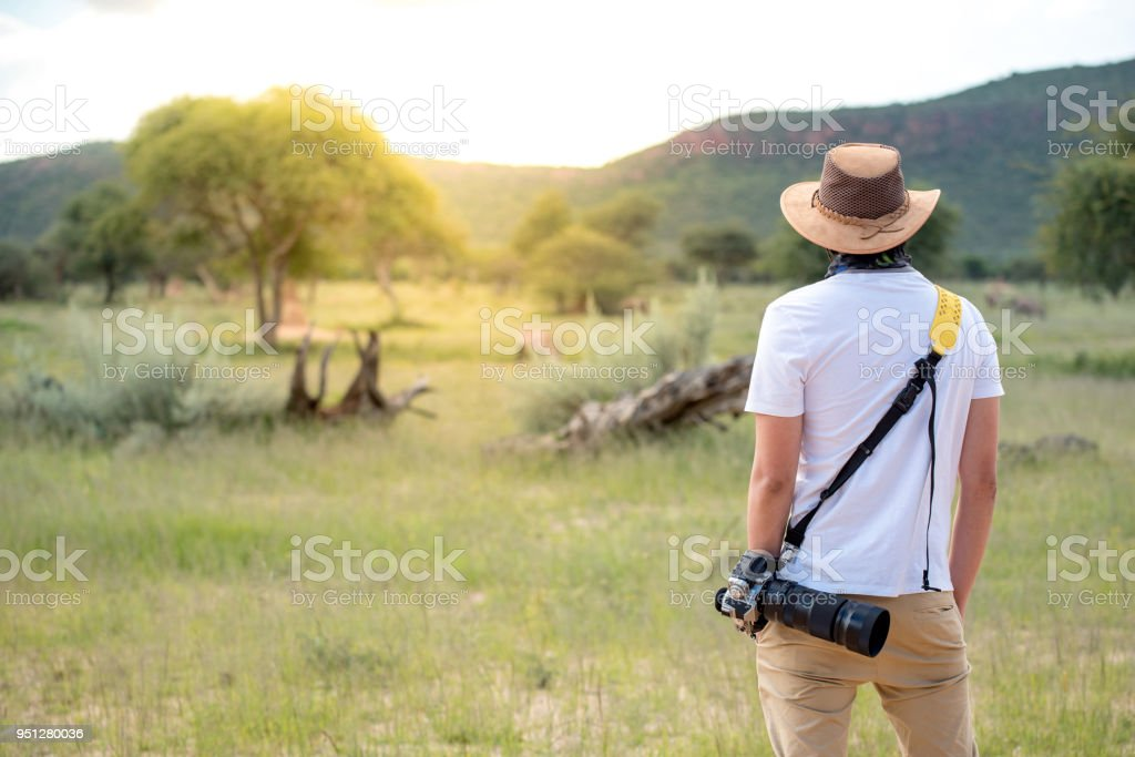 Young man traveler and photographer standing in safari looking at wildlife animals stock photo