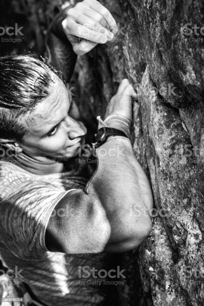 Young Man Traveler Climbing On Rock Wall. Achieving Goals Concept stock photo