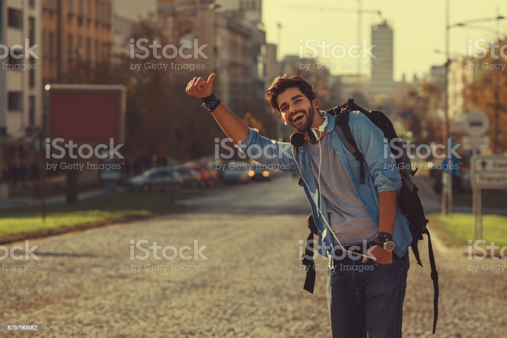 Young man traveler hitchhiking in the city stock photo