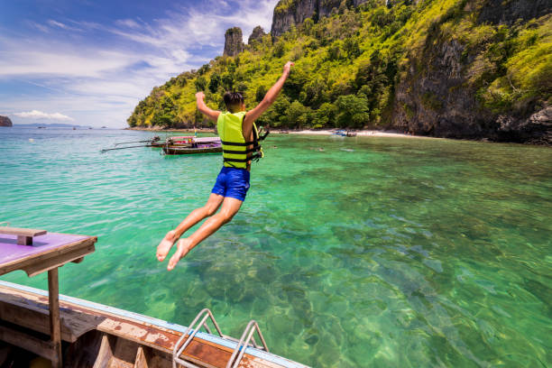 young man traveler jump into the sea form long thai boat at chicken island near railay beach in krabi province, thailand - phuket stock photos and pictures