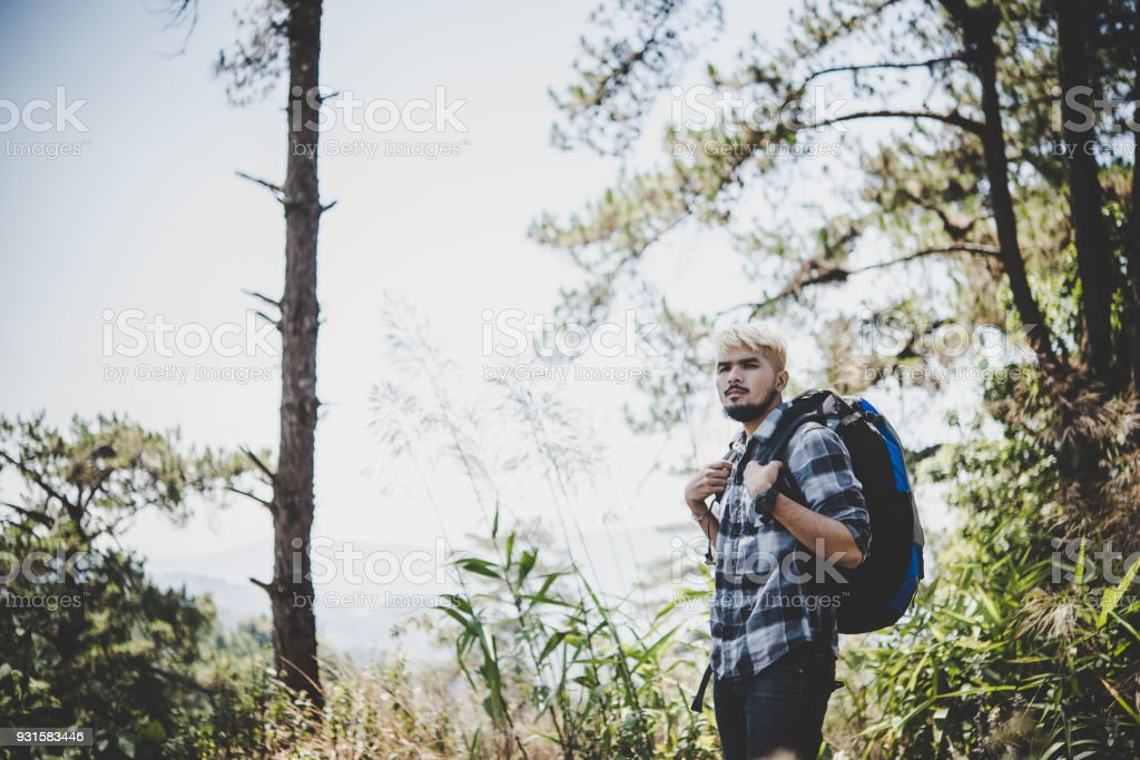 Young Man Traveler with backpack to mountain, Enjoying with nature around,Travel Lifestyle concept. stock photo