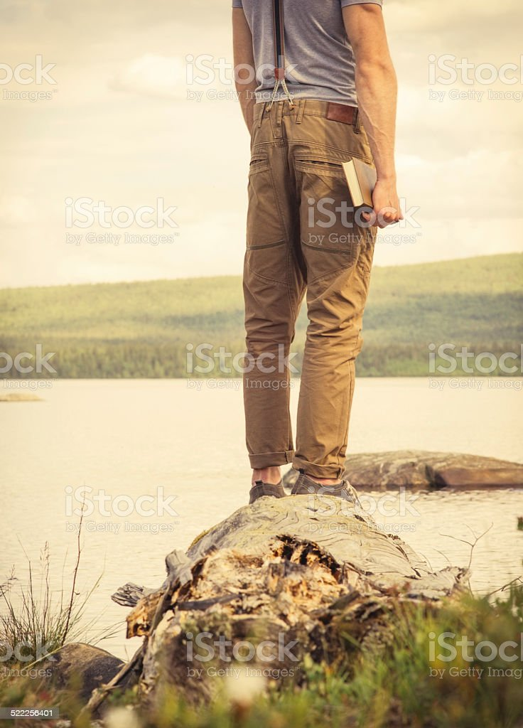 Young Man Traveler with book outdoor Travel Lifestyle stock photo