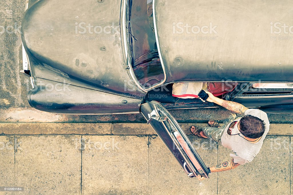 Young man traveler with tattoos watching phone at car trip stock photo