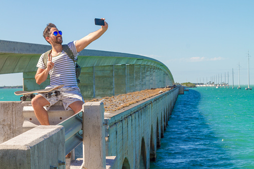 Young man traveling and taking a selfie by smartphone in Key West, Florida, USA in a summer hot sunny day