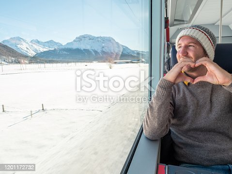 Travel man tourist in train visiting Switzerland enjoying beautiful panorama through window and making a heart shape frame with hands