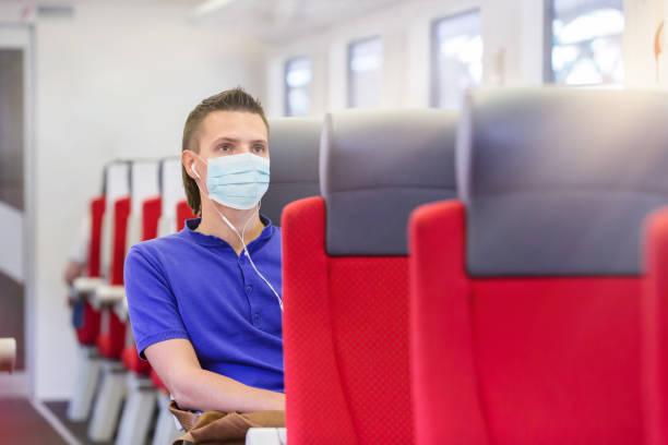 Junger Mann mit Schutzmaske mit Zug unterwegs – Foto