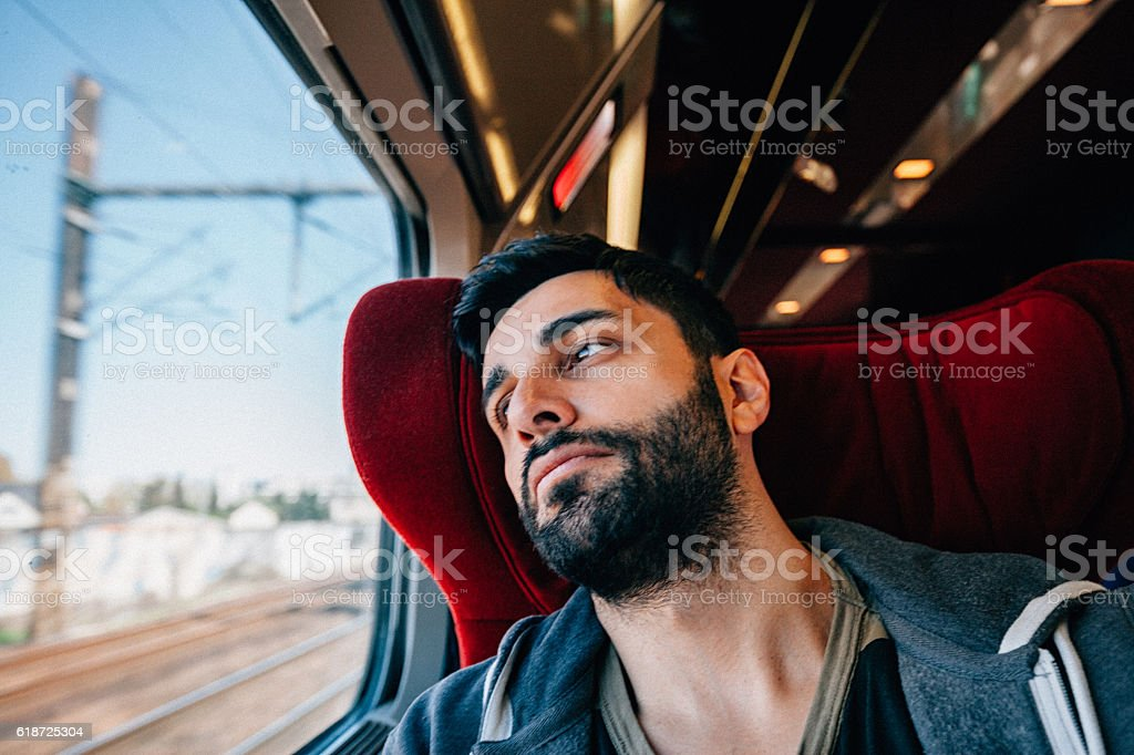Young Man Traveling In Train - Lost in thought stock photo
