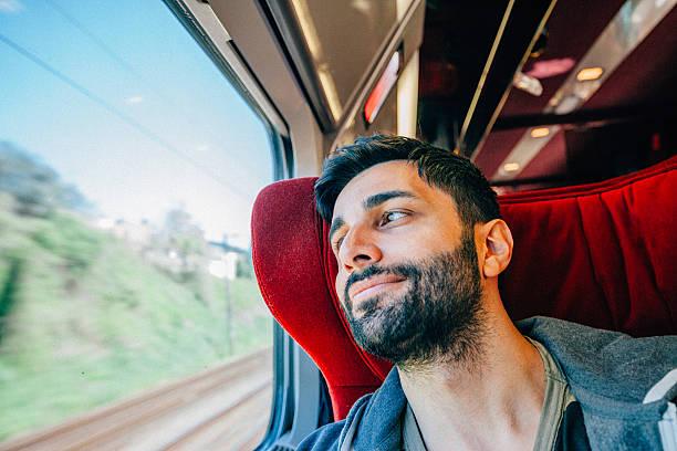 young man traveling in train - bahn bus stock-fotos und bilder