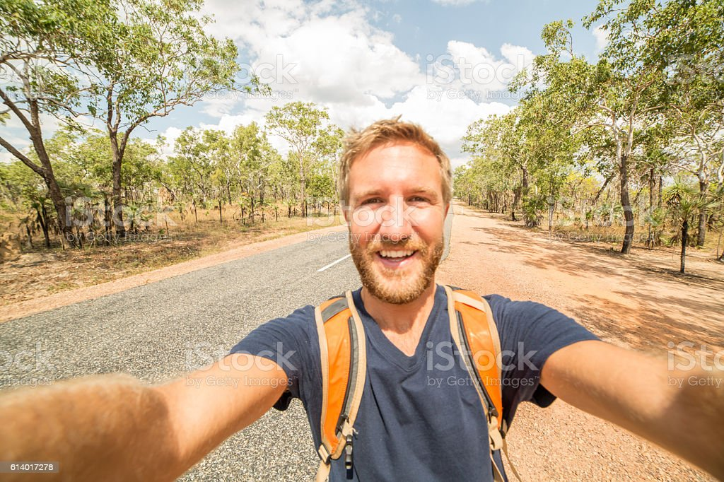 Young man traveling takes a selfie portrait on a road stock photo