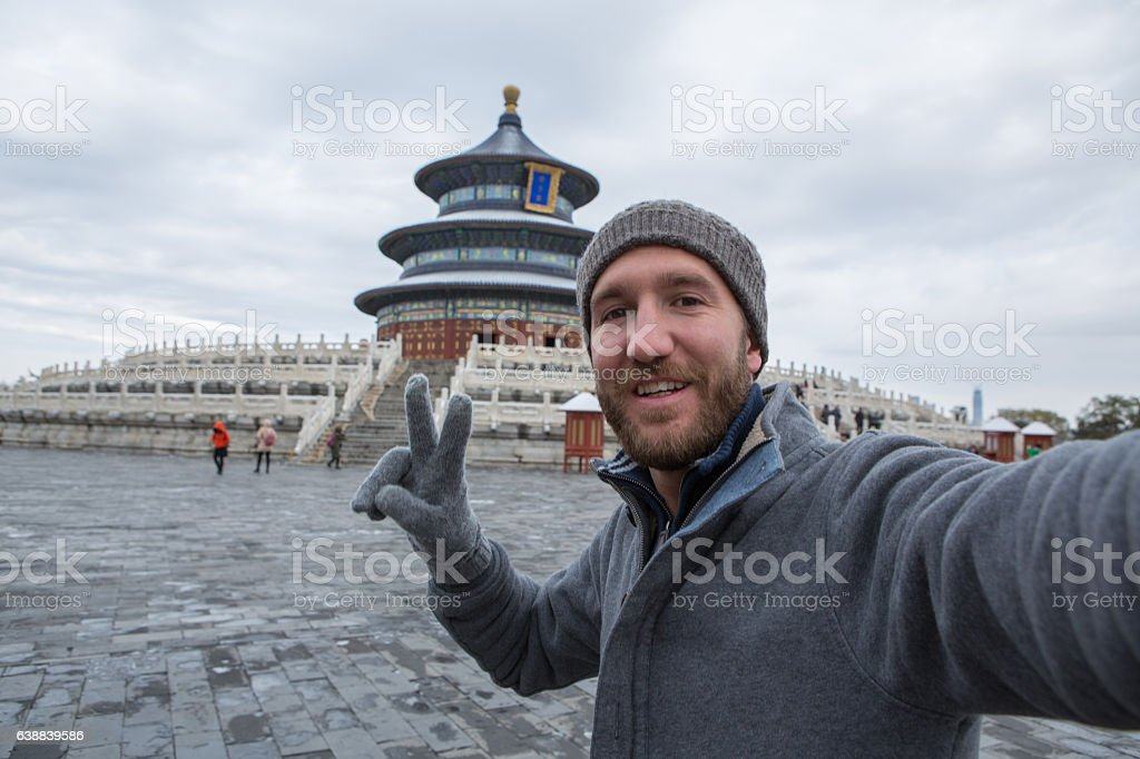 Young man traveling takes selfie with Temple of Heaven,Beijing stock photo