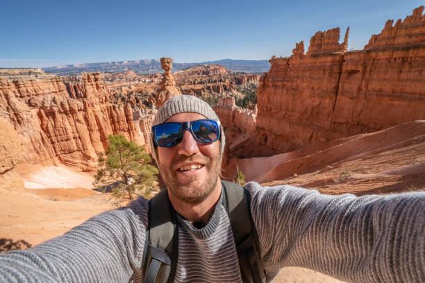 Young man travels Bryce in Utah takes selfie with awe nature on background stock photo