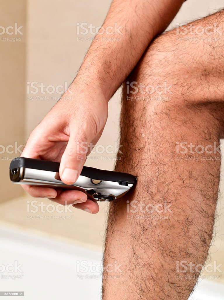 young man trimming his legs with an electric trimmer stock photo