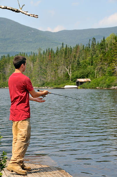 Young Man Trout Fishing on Mountain Lake stock photo