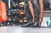 istock Young man try wearing new shoes in the store. shopping in the male store. 1213706731