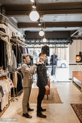 istock Young Man Trying on a New Suit 1210581191