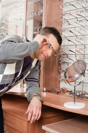 Young Man Trying On Glasses At Opticians Stock Photo - Download Image Now