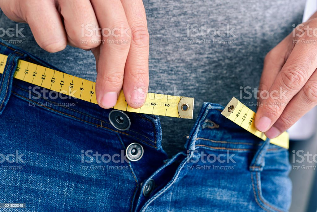 young man trying to fasten his trousers stock photo