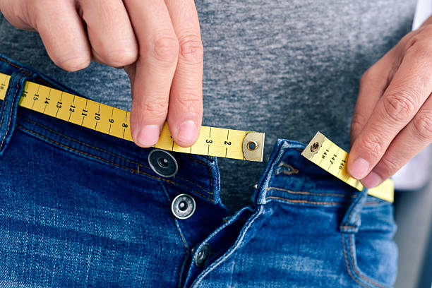 young man trying to fasten his trousers a young man with a measuring tape as a belt tries to fasten his trousers, because of the weight gain men in tight jeans stock pictures, royalty-free photos & images