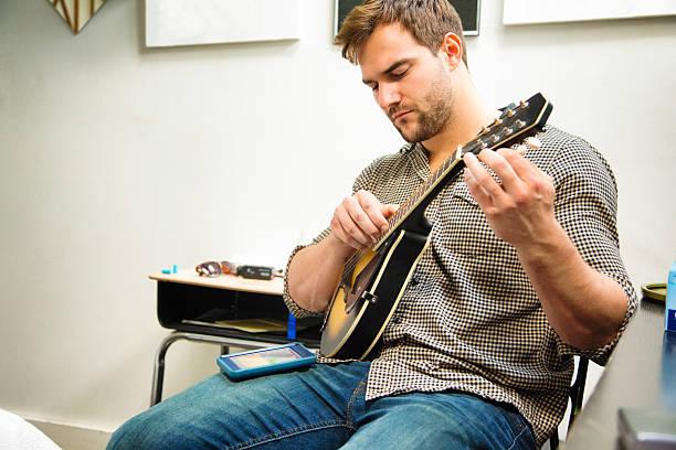 Jovem aperfeiçoar seu mandolin usando moble Aplicativo de telefone - foto de acervo