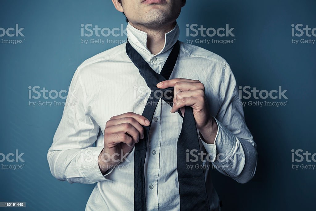Young man tying his tie stock photo
