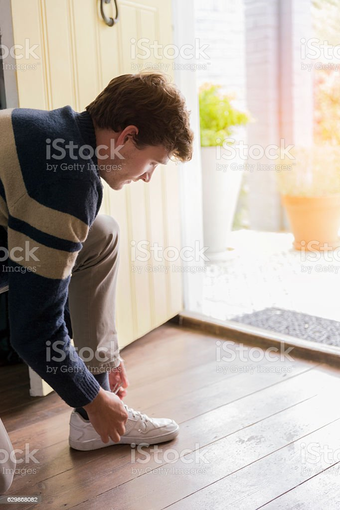 Young man tying shoelace at doorway stock photo