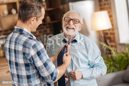 istock Young man tying the tie of his elderly father 893525204